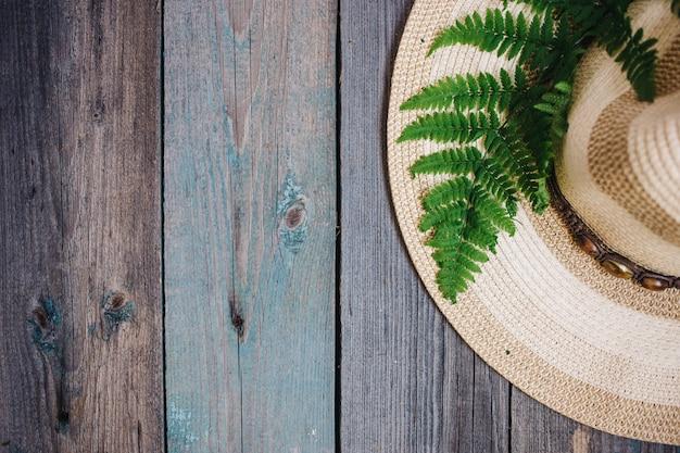 Un cappello, una foglia di felce sullo sfondo in legno, copia spazio