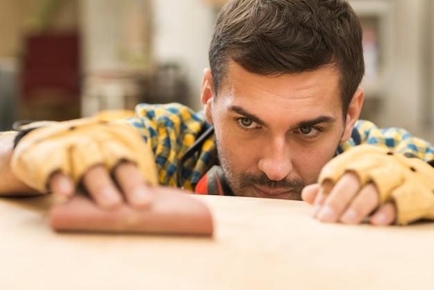 Un carpentiere maschio che utilizza carta vetrata sulla superficie di legno