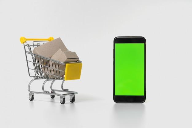 Un carrello accanto a uno smartphone su sfondo bianco