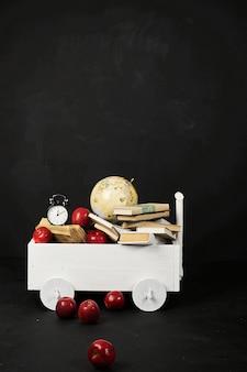 Un carrello bianco con un globo di libri e mele su sfondo nero