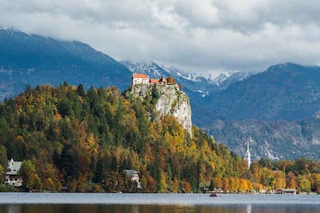 Un castello storico sulla cima di una collina coperta di foglie colorate a bled, slovenia