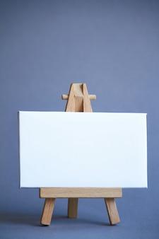 Un cavalletto in miniatura con un bordo bianco per la scrittura, puntatore sulla superficie bianca