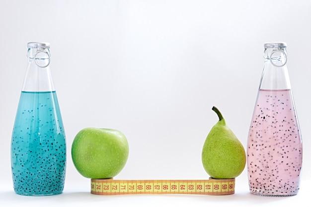 Un centimetro, una mela, una pera e bottiglie di vetro con semi di basilico rosa e blu stanno su uno sfondo bianco