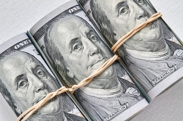 Un centinaio di banconote americane arrotolate come un tubulo. priorità bassa chiara, primo piano, fuoco selettivo