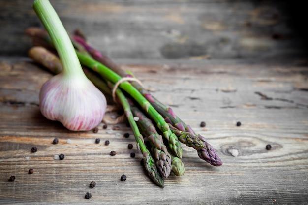Un certo aglio con un mazzo di asparagi su fondo di legno scuro, vista dell'angolo alto.