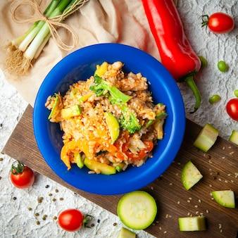 Un certo pasto delizioso con le cipolle verdi e pepe in un piatto blu su legno, panno rosso e fondo strutturato bianco, vista superiore.