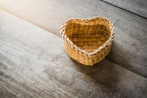 Un cestino a forma di cuore del rattan su fondo di legno