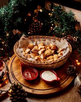 Un cestino di paglia con piccoli pani d'aglio servito con maionese e salsa di pomodoro