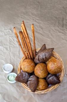 Un cesto di panini con pane marrone e piccanti e grissini