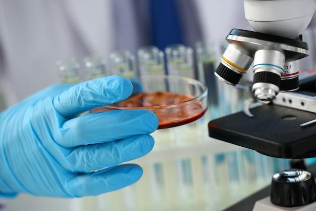 Un chimico maschio tiene in mano una provetta di vetro