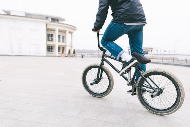 Un ciclista cavalca sulla bmx in piazza. un adolescente va in bicicletta in città. concetto bmx