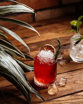 Un cocktail di frutta di vista frontale con i cubetti di ghiaccio sul succo del cocktail della bevanda della frutta dello scrittorio di legno marrone