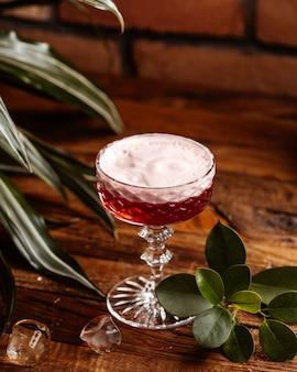 Un cocktail di frutta vista frontale con ghiaccio sul succo di bevanda cocktail scrivania in legno marrone
