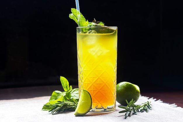 Un cocktail estivo rinfrescante con una fetta di lime. bevanda alcolica. guarnito con un rametto di menta e cubetti di ghiaccio. nel bar
