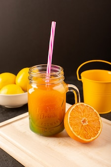 Un cocktail freddo vista frontale colorato all'interno di lattine di vetro con limoni di paglia colorati fiori sulla scrivania in legno crema e buio