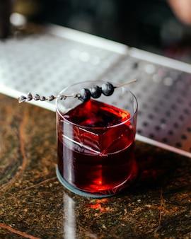 Un cocktail rosso di vista superiore all'interno del piccolo bicchiere sull'acqua del succo di alcool della bevanda dello scrittorio della barra