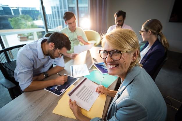 Un collega che sorride alla macchina fotografica mentre collega che discute sopra il grafico