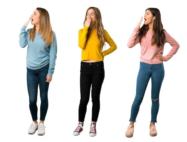 Un colpo a figura intera di un gruppo di persone con abiti colorati che sbadigliano