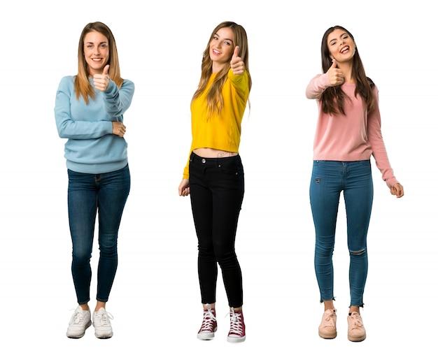 Un colpo a figura intera di un gruppo di persone con abiti colorati dando un pollice in alto gesto