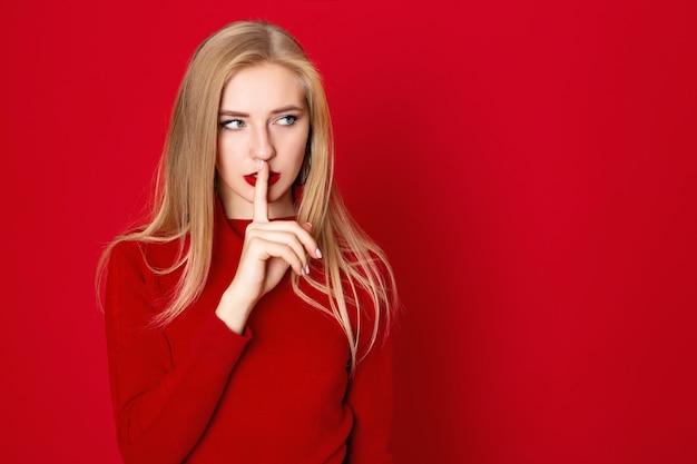 Un colpo da studio di ragazza longhair blone indossa una maglietta rossa casual