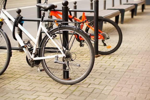 Un colpo del primo piano di angolo basso di due biciclette parcheggiate sul marciapiede