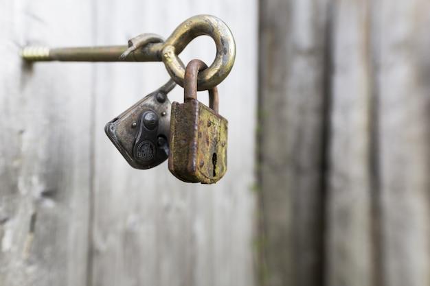 Un colpo del primo piano di due serrature arrugginite su una maniglia del metallo