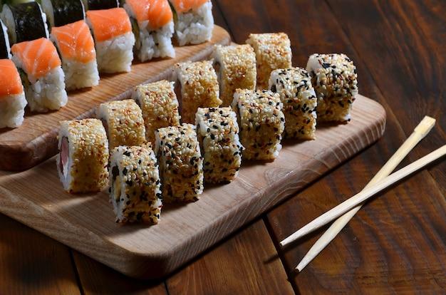 Un colpo dettagliato di una serie di rotolini di sushi giapponesi e un dispositivo per il loro uso bacchette