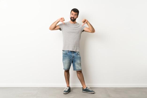 Un colpo di lunghezza di bell'uomo con la barba che mostra il pollice verso il basso