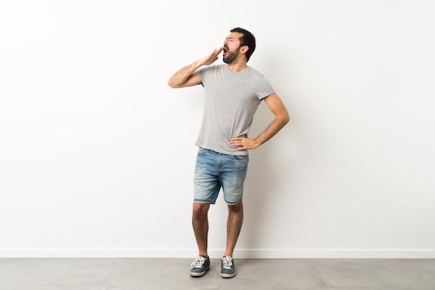 Un colpo di lunghezza di bell'uomo con la barba che sbadiglia e che copre la bocca spalancata con la mano