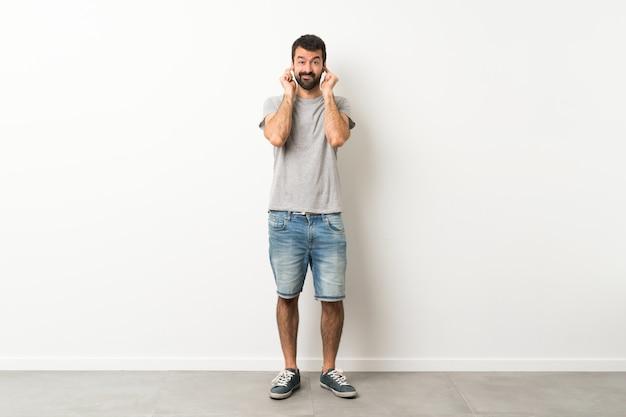 Un colpo di lunghezza di bell'uomo con la barba frustrata e che copre le orecchie