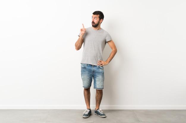 Un colpo di lunghezza di bell'uomo con la barba pensando un'idea che punta il dito verso l'alto