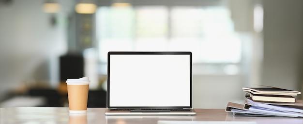 Un computer portatile con schermo vuoto bianco sta mettendo su un tavolo bianco circondato da una tazza di caffè e da una pila di libri.