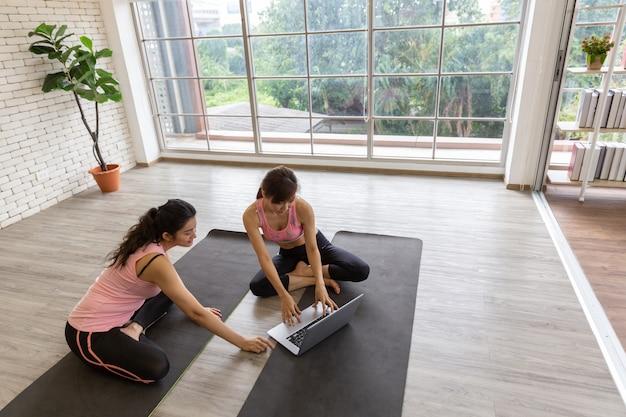 Un computer portatile dall'aspetto femminile due asiatici impara la formazione yoga da internet