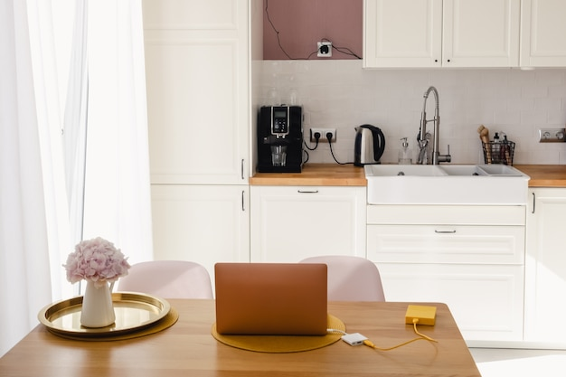 Un computer portatile e un vaso con fiori sul tavolo da pranzo in legno in cucina in una luminosa giornata di sole