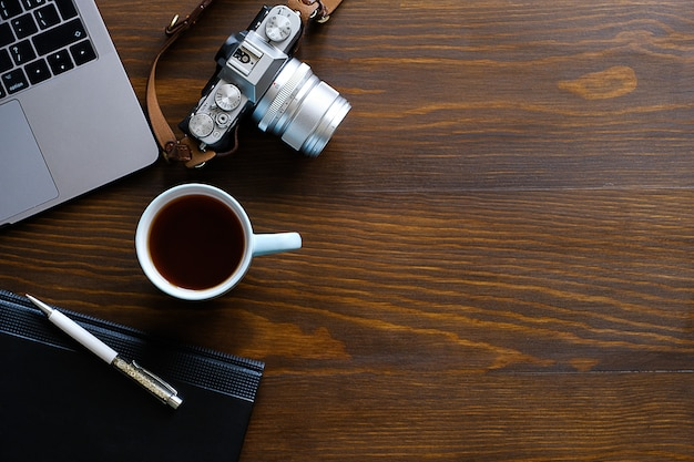 Un computer portatile, una tazza di tè, una macchina fotografica e un taccuino si trovano su un tavolo di legno scuro.