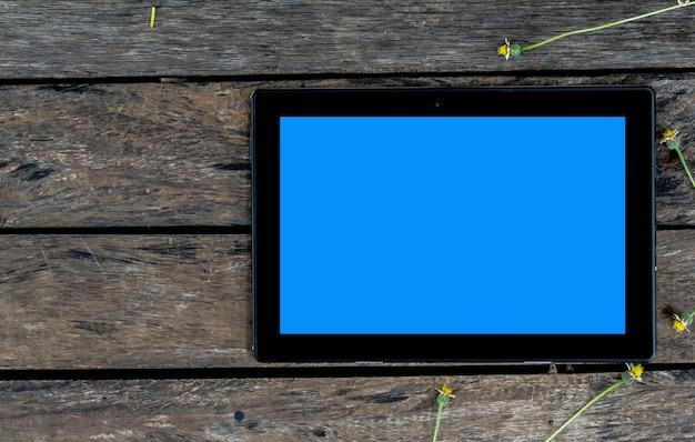 Un computer tablet nero con schermo blu sul vecchio tavolo di legno.