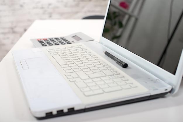 Un computer, una calcolatrice e una penna su una scrivania