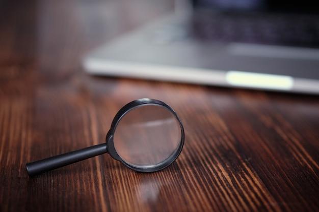 Un concetto astratto di una lente d'ingrandimento e un computer portatile come ricerca di informazioni in uno stagista per le imprese.
