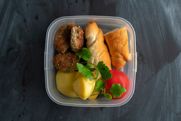 Un concetto di ora di pranzo, mangiare dal contenitore di plastica con carne e patate sui tavoli
