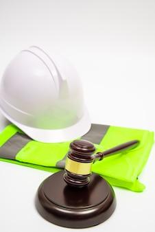 Un concetto legale relativo al lavoro con cappelli di sicurezza, abiti da lavoro e un martelletto del giudice su uno sfondo bianco. con spazio di copia.
