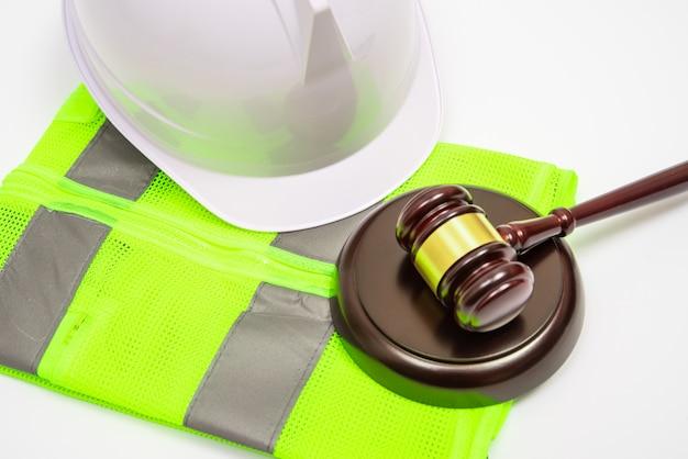 Un concetto legale relativo al lavoro con cappelli di sicurezza, abiti da lavoro e un martelletto del giudice su uno sfondo bianco.