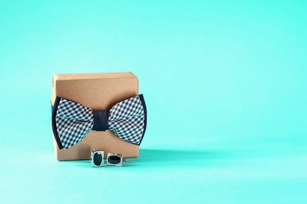 Un contenitore di regalo avvolto in carta del mestiere e legato con il farfallino sul blu. festa del papà.