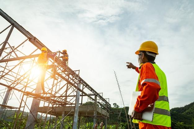 Un controllo del muratore nel tecnico dell'ingegnere che guarda gruppo di lavoratori sull'alta piattaforma d'acciaio, tecnico dell'ingegnere che cerca e che analizza un progetto di costruzione non finito.