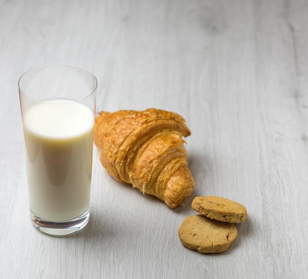 Un cornetto, dei biscotti e un bicchiere di latte