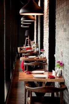 Un corridoio ristorante con piccoli tavoli da due persone