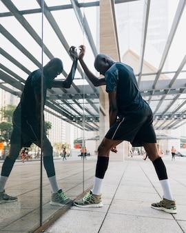 Un corridore maschio che allunga il suo muscolo in piedi davanti al vetro