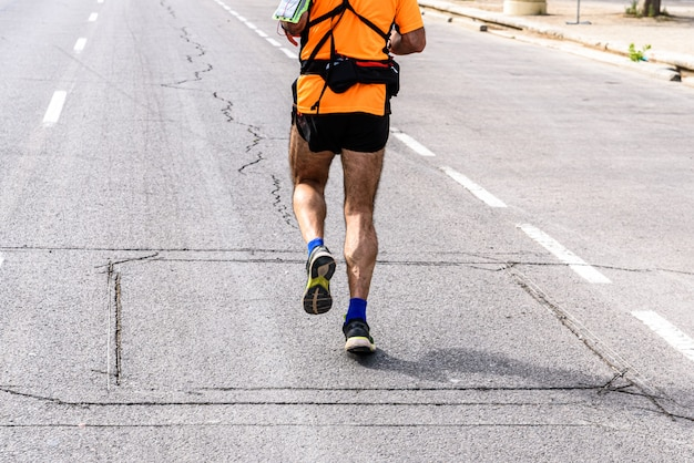 Un corridore uomo maturo dotato di marsupio che fa sport per allenare le gambe