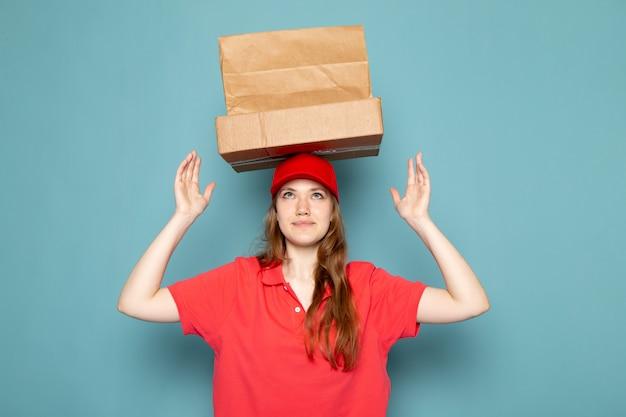 Un corriere attraente femminile di vista frontale in spiritello malevolo rosso che tiene i pacchetti marroni sopra la sua testa che posa sul lavoro blu di servizio ristoro del fondo