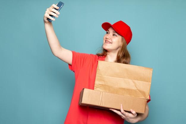 Un corriere attraente femminile di vista frontale in spiritello malevolo rosso della camicia di polo che tiene pacchetto marrone che prende un selfie sul lavoro blu di servizio ristoro del fondo