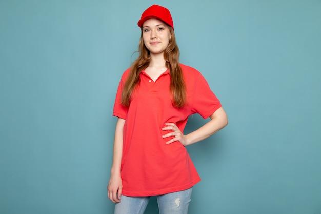 Un corriere attraente femminile di vista frontale in spiritello malevolo rosso della camicia di polo e jeans che posano sul lavoro blu di servizio ristoro del fondo